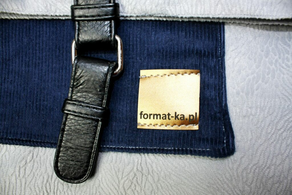Metka Format-ki na torebce Julia, granatowa sztruksowa kieszrń i klamra z ekoskóry.