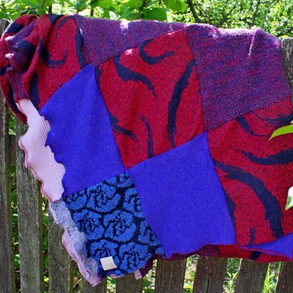 Cześć koca przedstawiająca kwadraty w kolorze śliwkowym, fioletowym i błękitnym.