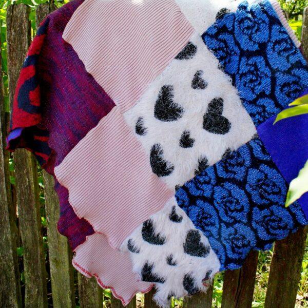 Część koca przedstawiająca patchworkowe części w kolorze pudrowym, głęboko niebieskim i szarym, włochatym w serca.
