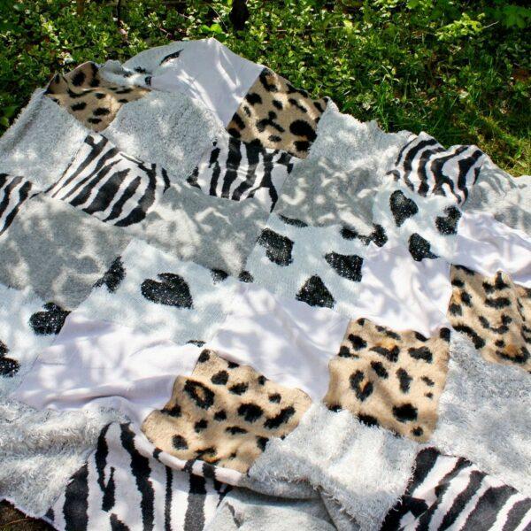 Patchworkowy koc sawanna rozłożony na trawie, elementy swetrów w paski zebry i cętki tygrysa.