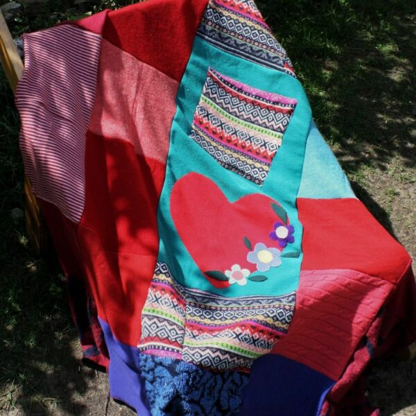 patchworkowy koc z naszytym sercem rozłożony na leżaku.