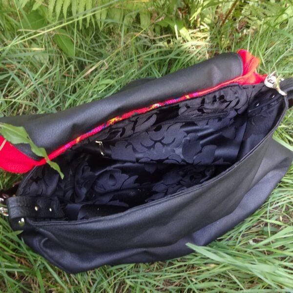 Wnętrze torby listonoszki z ekoskóry i czerwonej chusty.