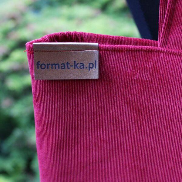 Złota metka Format-ki na czerwonej szoperce.