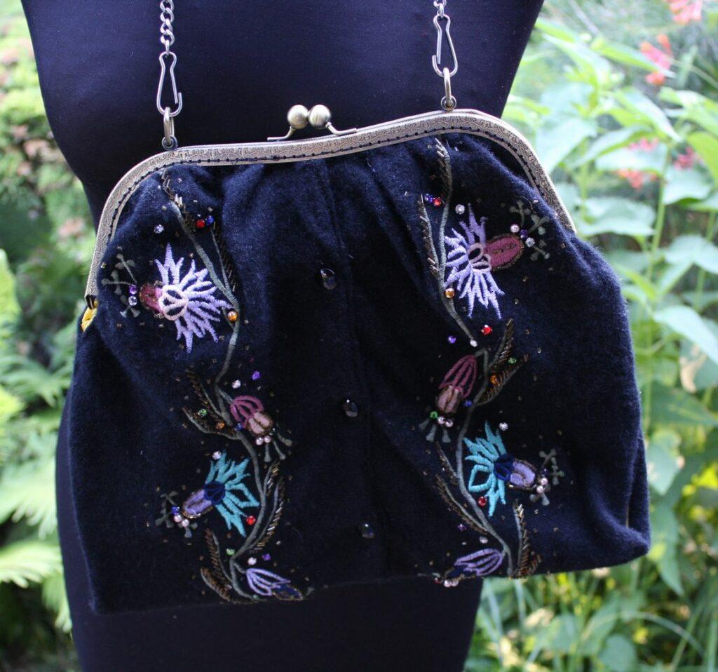 Ręcznie szyta torebka z moherowego swetra z koralikami, z biglem i łańcuszkiem na manekinie.