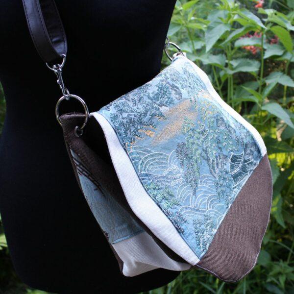 Bok torebki listonoszki z materiałów upcyclingowych.