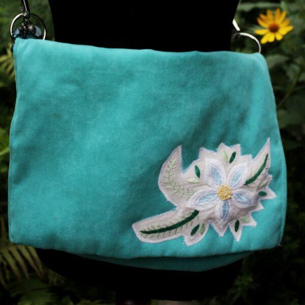 Morska kopertówka z haftowanym kwiatem z obrusa.